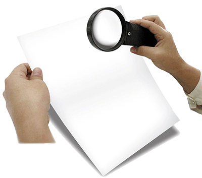 hands holding magnifying glass looking at paper
